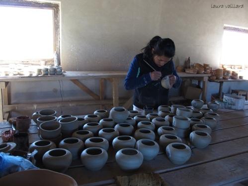 Artesana pinta las vasijas a mano
